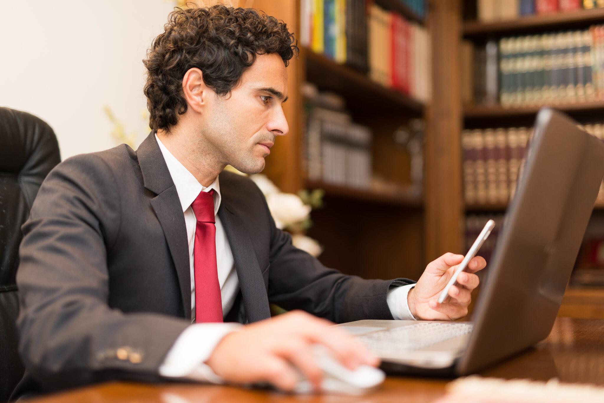 Juriste avec une belle cravate rouge sur son pc et son smartphone MGA